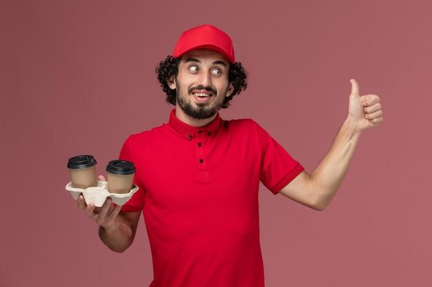 Вид спереди мужчина-курьер-курьер в красной рубашке и плаще, держащий коричневые кофейные чашки на светло-розовой стене, служащий службы доставки