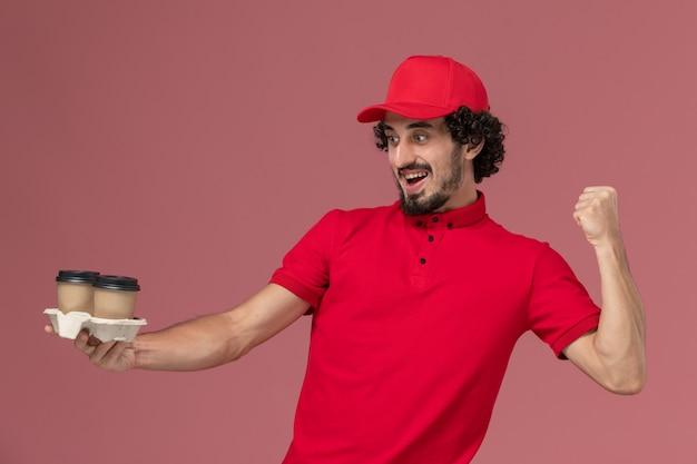 Вид спереди мужчина-курьер-доставщик в красной рубашке и плаще, держащий коричневые кофейные чашки доставки на светло-розовой стене, служащий службы доставки