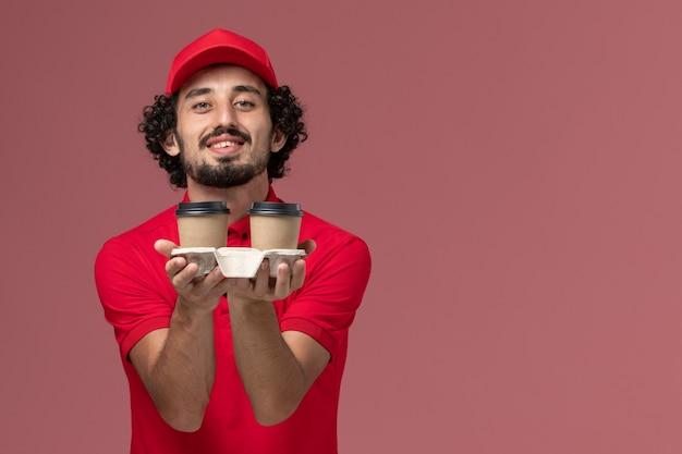 ピンクの壁の仕事サービス配達従業員に茶色の配達コーヒーカップを保持している赤いシャツと岬の正面図男性宅配便配達人