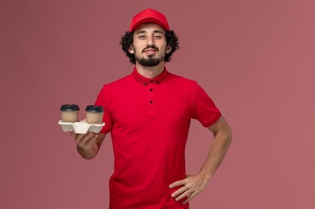 ピンクの壁に茶色の配達コーヒーカップを保持している赤いシャツとケープの正面図男性宅配便配達人サービス配達従業員の仕事