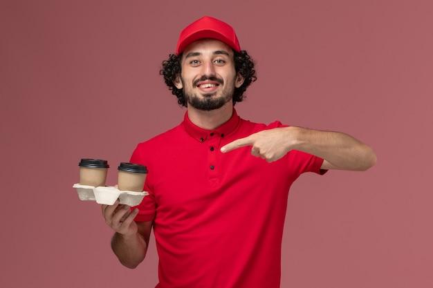 ピンクの壁のサービス配達従業員に茶色の配達コーヒーカップを保持している赤いシャツとケープの正面図男性宅配便配達人