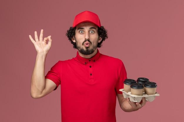 Вид спереди мужчина курьерской службы доставки в красной рубашке и накидке, держащий коричневые кофейные чашки доставки на светло-розовой стене, работа сотрудника службы доставки компании