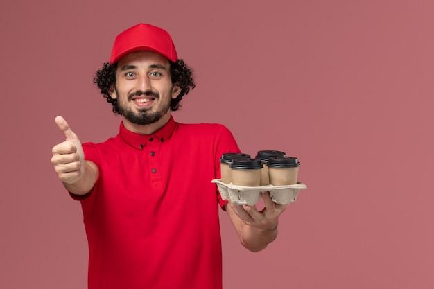 淡いピンクの壁のサービス配達従業員会社で茶色の配達コーヒーカップを保持している赤いシャツとケープの正面図男性宅配便配達人
