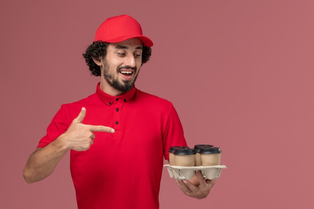 淡いピンクの壁のサービス配達従業員に茶色の配達コーヒーカップを保持している赤いシャツとケープの正面図男性宅配便配達人