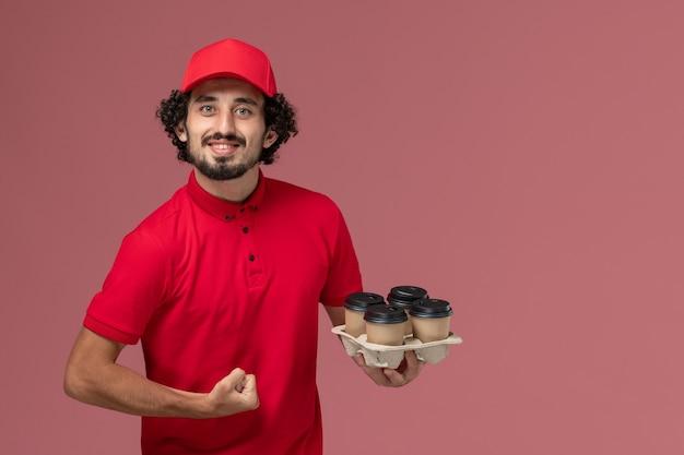 빨간 셔츠와 케이프 라이트 핑크 벽 서비스 작업 배달 직원에 갈색 배달 커피 컵을 들고 전면보기 남성 택배 배달 남자