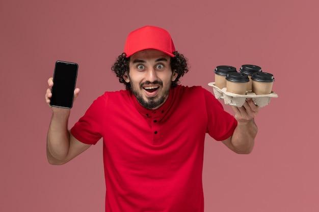 ピンクの壁のサービス配達従業員労働者に電話で茶色の配達コーヒーカップを保持している赤いシャツと岬の正面図男性宅配便配達人