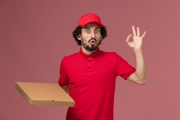 ピンクの壁に配達フードボックスを保持している赤いシャツと岬の正面図男性宅配便配達会社従業員の仕事の仕事