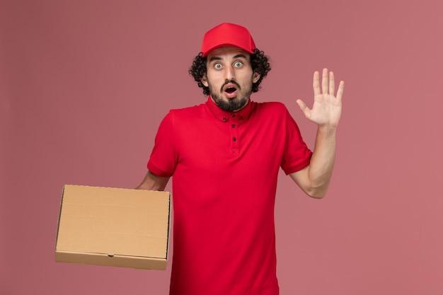 Вид спереди мужчина курьерской службы доставки в красной рубашке и накидке, держащий коробку с едой на розовой стене, работа сотрудника компании по доставке услуг