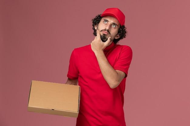 ピンクの壁のサービス配達会社の従業員男性を考えて配達フードボックスを保持している赤いシャツとケープの正面図男性宅配便配達人