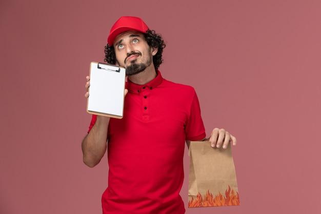 ピンクの壁のサービス配達の従業員を考えているだけで食品パッケージとメモ帳を保持している赤いシャツとケープの正面図男性宅配便配達人