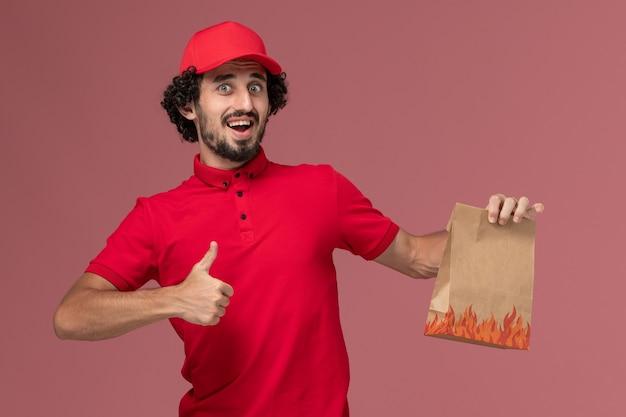 Вид спереди мужчина курьерской службы доставки в красной рубашке и накидке, держащий пакет с едой на розовой стене, работа сотрудника службы доставки