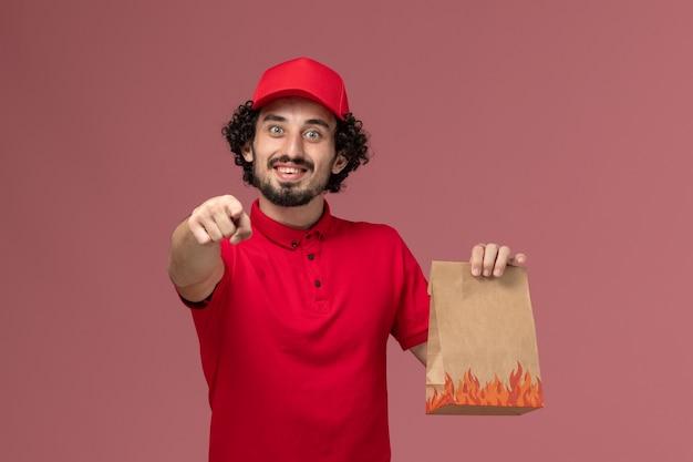 빨간 셔츠와 케이프 핑크 벽 서비스 작업 작업 배달 회사 직원에 음식 패키지를 들고 전면보기 남성 택배 배달 남자