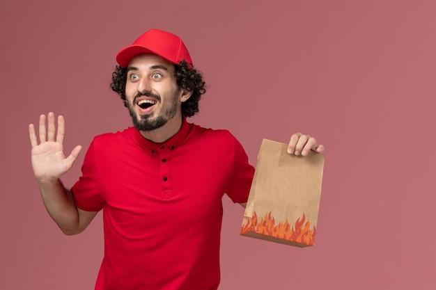 ピンクの壁のサービス配達会社の従業員を喜んで食品パッケージを保持している赤いシャツとケープの正面図男性宅配便配達人