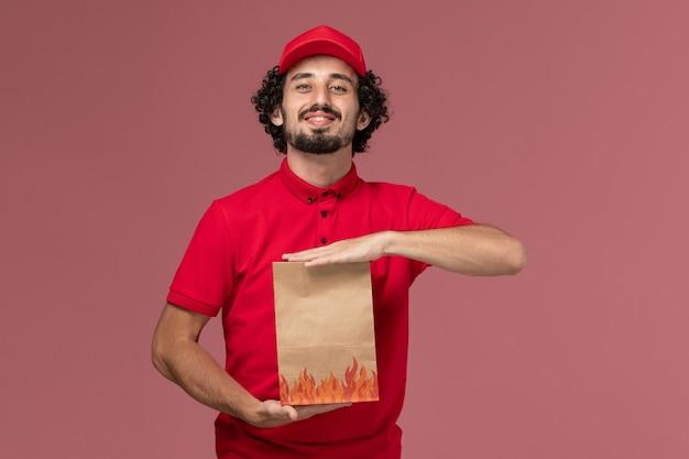 ピンクの壁のサービス配達会社の従業員の仕事で紙の食品パッケージを保持している赤いシャツと岬の正面図男性宅配便配達人