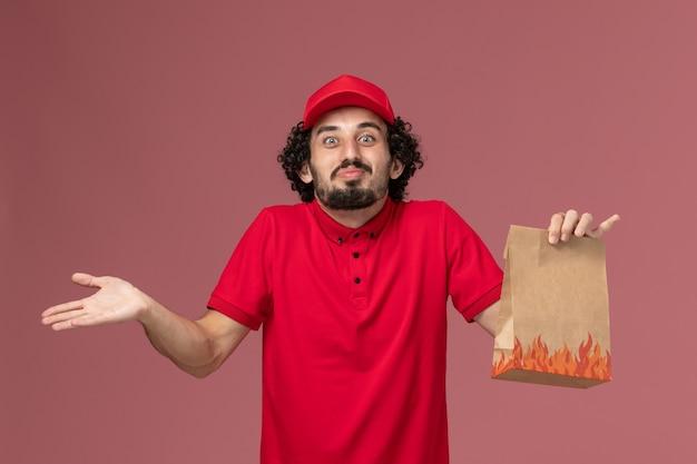ピンクの壁のサービス配達会社の従業員に紙の食品パッケージを保持している赤いシャツとケープの正面図男性宅配便配達人