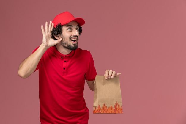 ピンクの壁のサービス配達会社の従業員に聞いてみようとしている赤いシャツとケープ保持紙食品パッケージの正面図男性宅配便