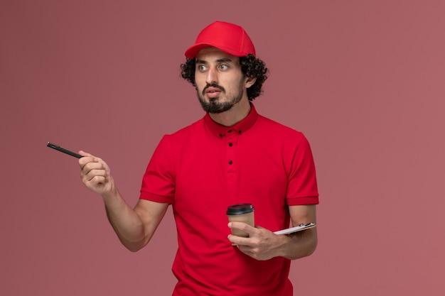 Uomo di consegna corriere maschio vista frontale in camicia rossa e mantello che tiene tazza di caffè marrone e blocco note con la penna sul lavoro dipendente consegna servizio parete rosa chiaro