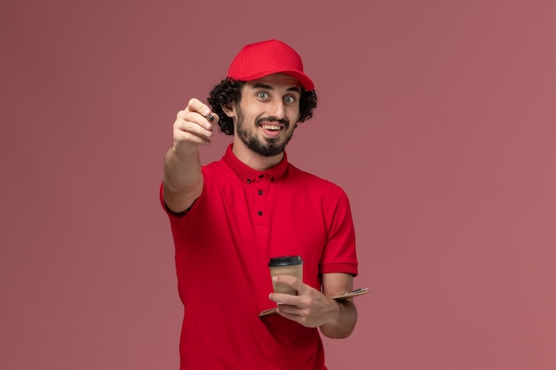 Front view male courier delivery man in red shirt and cape holding brown coffee cup and notepad with pen on light pink wall service delivery employee worker