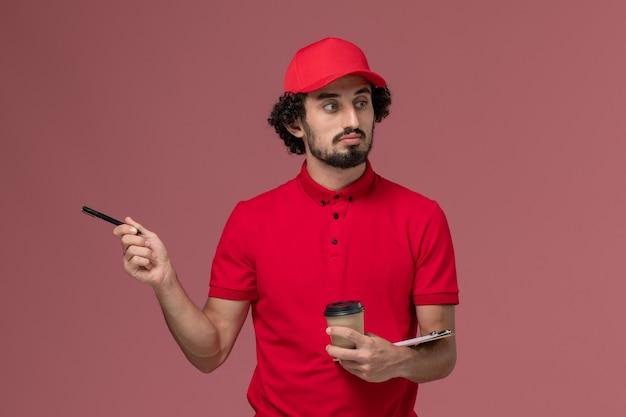 Uomo di consegna corriere maschio vista frontale in camicia rossa e mantello che tiene tazza di caffè marrone e blocco note con la penna sul dipendente di consegna servizio parete rosa chiaro