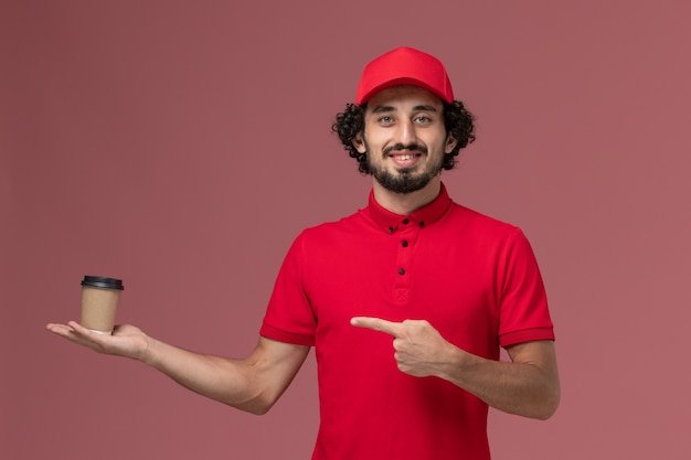 Front view male courier delivery man in red shirt and cape holding brown coffee cup on pink wall service uniform delivery employee male work