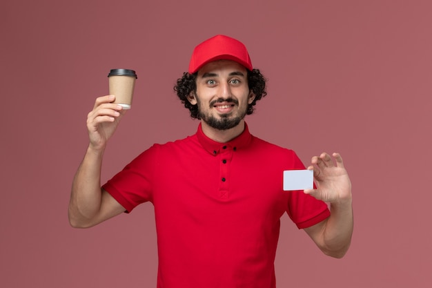 Front view male courier delivery man in red shirt and cape holding brown coffee cup with card on light-pink wall service uniform delivery employee job