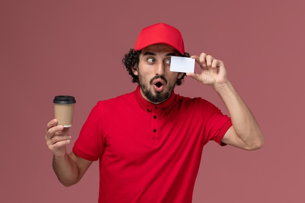 Front view male courier delivery man in red shirt and cape holding brown coffee cup with card on light-pink wall service uniform delivery employee work