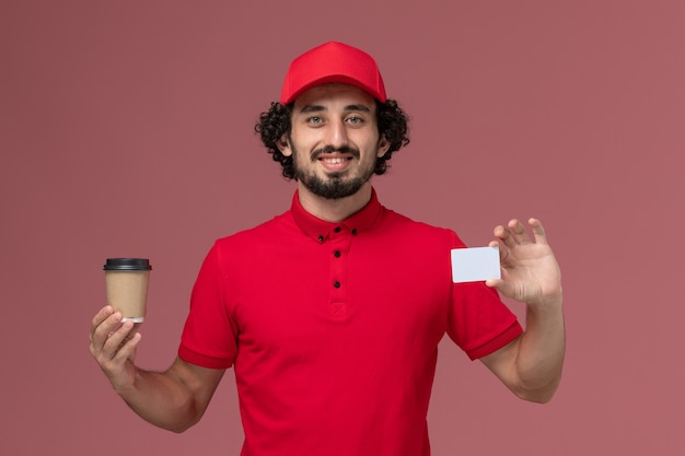 Front view male courier delivery man in red shirt and cape holding brown coffee cup with card on light-pink wall service uniform delivery employee
