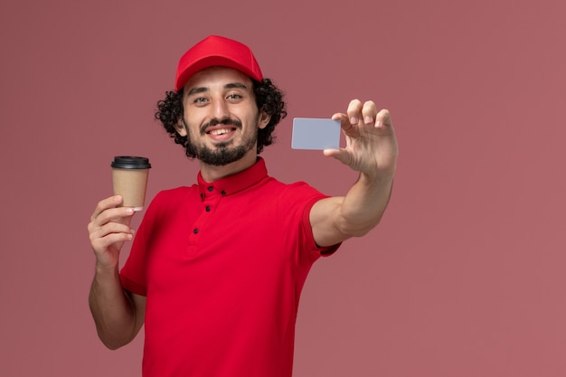 Front view male courier delivery man in red shirt and cape holding brown coffee cup with grey card on light-pink wall service uniform delivery employee male