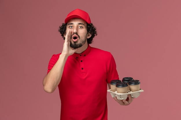 Front view male courier delivery man in red shirt and cape holding brown delivery coffee cups calling out on the light pink wall service delivery employee