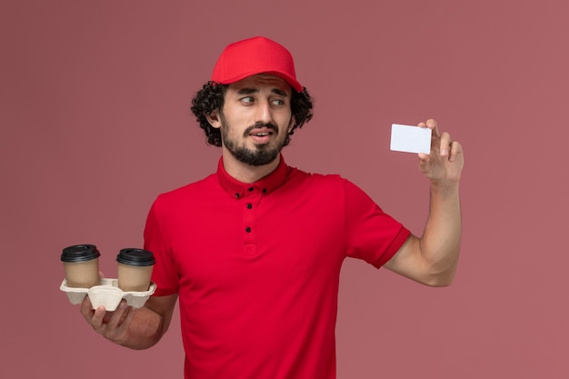 Front view male courier delivery man in red shirt and cape holding brown delivery coffee cups and card on light-pink wall service delivery employee job