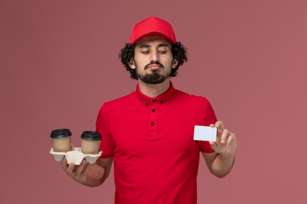Front view male courier delivery man in red shirt and cape holding brown delivery coffee cups and card on light-pink wall service delivery employee male