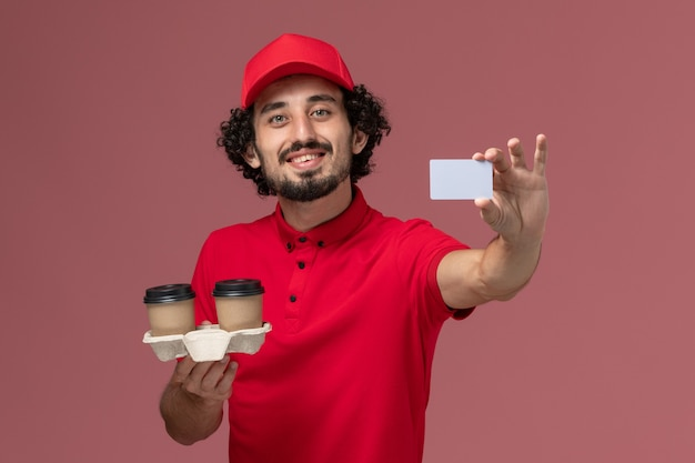 Front view male courier delivery man in red shirt and cape holding brown delivery coffee cups and card smiling on light-pink wall service delivery employee