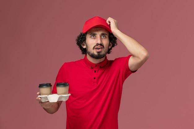 Uomo di consegna maschio del corriere di vista frontale in camicia rossa e mantello che tiene le tazze di caffè marroni di consegna sul maschio rosa chiaro dell'impiegato di consegna di servizio della parete
