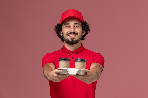 Front view male courier delivery man in red shirt and cape holding brown delivery coffee cups on light-pink wall service delivery job employee