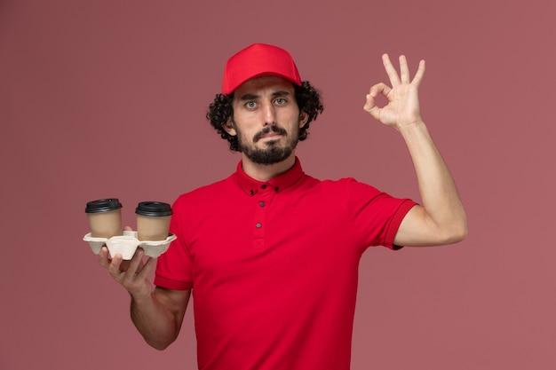 Uomo di consegna maschio del corriere di vista frontale in camicia rossa e mantello che tiene le tazze di caffè marroni di consegna sull'impiegato di consegna di lavoro di servizio della parete rosa-chiaro