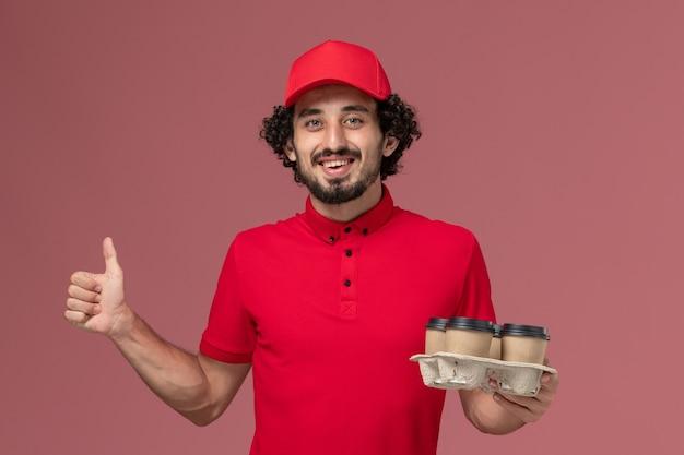 Uomo di consegna maschio del corriere di vista frontale in camicia rossa e mantello che tiene le tazze di caffè marroni di consegna sull'impiegato di consegna del lavoro di servizio della parete rosa chiaro