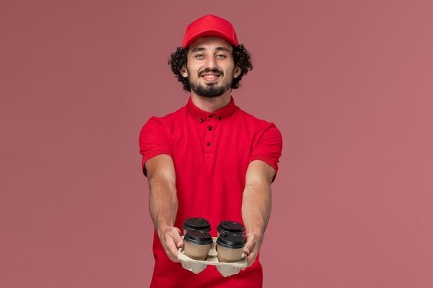 Uomo di consegna maschio del corriere di vista frontale in camicia rossa e mantello che tiene le tazze di caffè marroni di consegna sull'impiegato di lavoro di consegna del lavoratore di servizio della parete rosa-chiaro