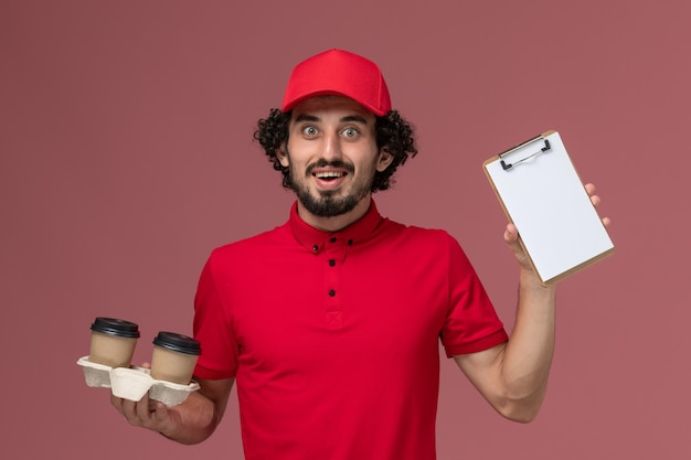 Front view male courier delivery man in red shirt and cape holding brown delivery coffee cups and notepad on the light-pink wall service delivery employee job work