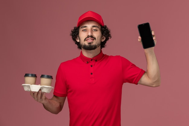 Front view male courier delivery man in red shirt and cape holding brown delivery coffee cups and phone on the light-pink wall service delivery employee job