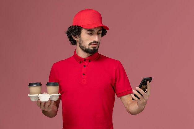 Front view male courier delivery man in red shirt and cape holding brown delivery coffee cups and phone on the light-pink wall service delivery employee male