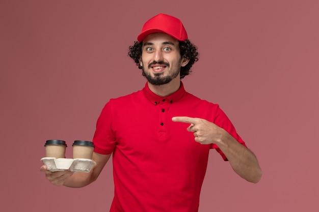 Uomo di consegna maschio del corriere di vista frontale in camicia rossa e mantello che tiene le tazze di caffè marroni di consegna sul lavoro maschio dell'impiegato di consegna di servizio della parete rosa