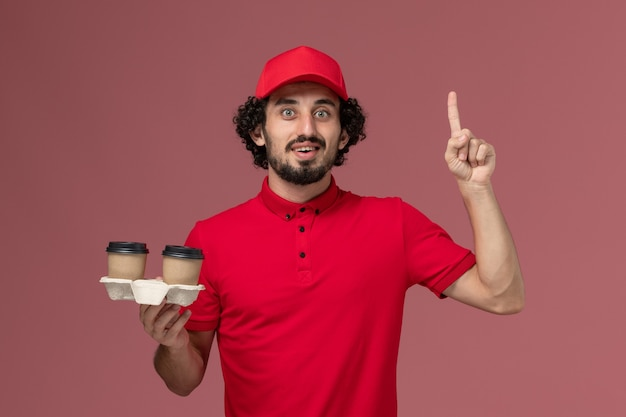 Front view male courier delivery man in red shirt and cape holding brown delivery coffee cups on pink wall service delivery employee worker