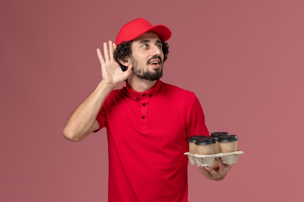 Front view male courier delivery man in red shirt and cape holding brown delivery coffee cups and trying to hear something on pink wall service delivery employee