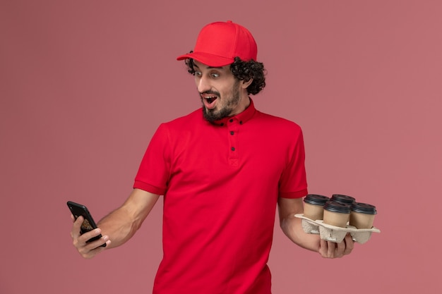 Front view male courier delivery man in red shirt and cape holding brown delivery coffee cups with phone on the light pink wall male service delivery worker employee