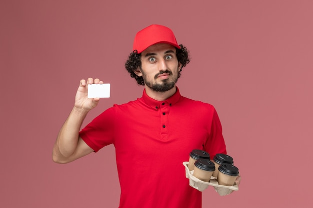 Front view male courier delivery man in red shirt and cape holding brown delivery coffee cups with plastic card on the pink wall service delivery employee job