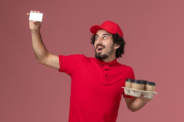 Front view male courier delivery man in red shirt and cape holding brown delivery coffee cups with plastic card on the pink wall service delivery employee male