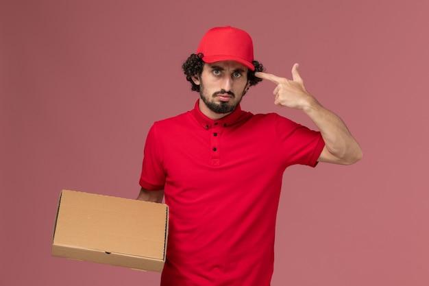 Uomo di consegna maschio del corriere di vista frontale in camicia rossa e mantello che tiene la scatola dell'alimento di consegna sul lavoratore dipendente della società di consegna di servizio della parete rosa