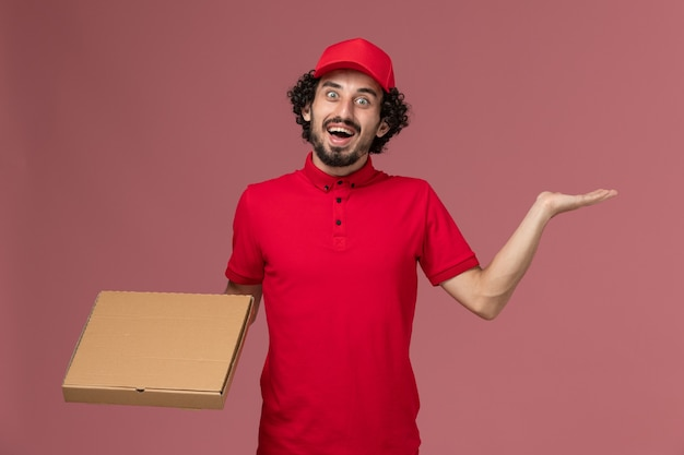 Front view male courier delivery man in red shirt and cape holding delivery food box on the pink wall service delivery company employee