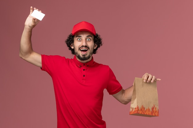 Front view male courier delivery man in red shirt and cape holding food package and card on the pink wall service delivery employee work