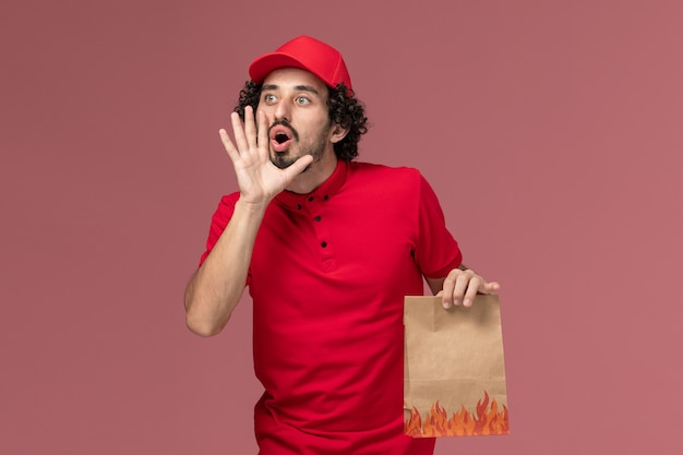Front view male courier delivery man in red shirt and cape holding paper food package and calling out someone on pink desk service delivery company employee